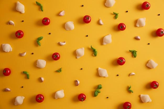Vista dall'alto piatto di gusci di pasta di grano duro, pomodorini rossi, basilico e aglio per preparare il piatto italiano. verdure e spezie su sfondo giallo. ingredienti da cucina. cibo disintossicante