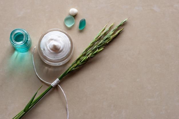 Плоский вид баночка кремовых колосков с белой веревкой две стеклянные куклы и камешек выборочный фокус