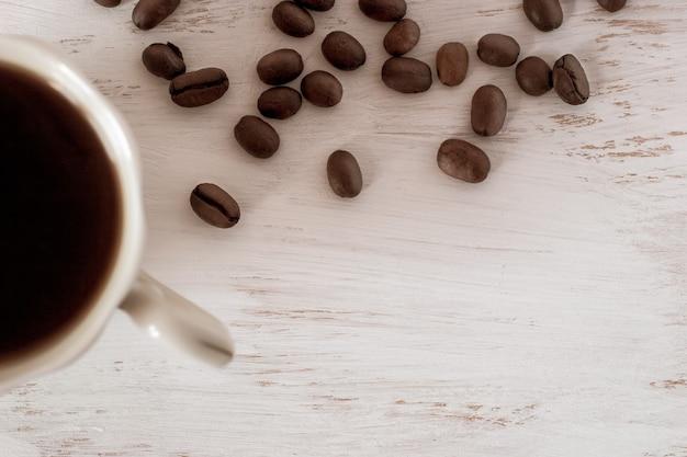 フラットビュー。白い背景の上のコーヒーと散らばったコーヒー豆とコーヒーカップの半分。あなたのテキストのための場所。
