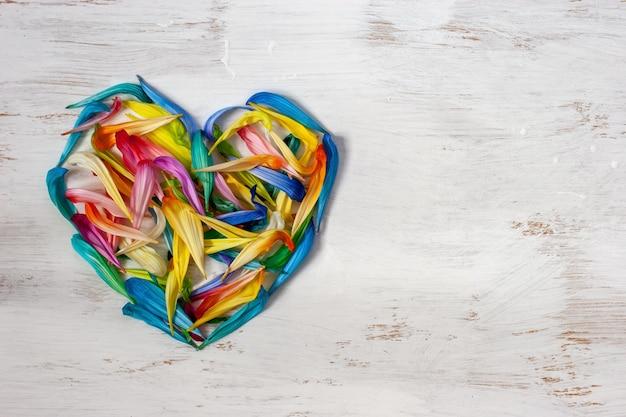 Плоский вид сердце из цветных лепестков цветов на белом фоне с местом для текста символ любви