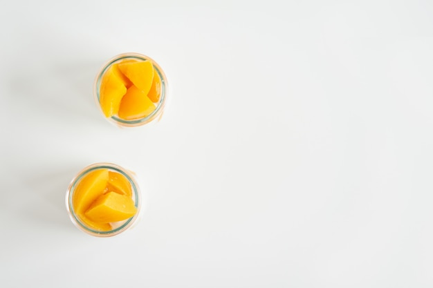 Flat view of jars of greek yogurt with canned apricots top view