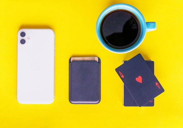 Flat view mobile wallet cards cup of coffee yellow background