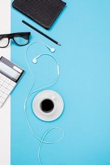 デスクトップ用の文房具とノートブックの創造的な配置を備えたオフィスデスクのフラットビュー