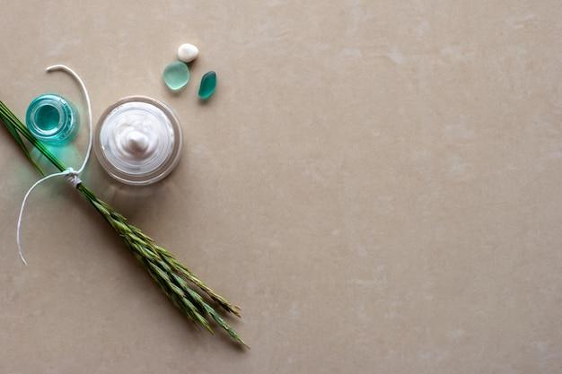 Плоский вид колоски, перевязанные белой веревкой, баночка с белым кремом, камешек и два кусочка стекла