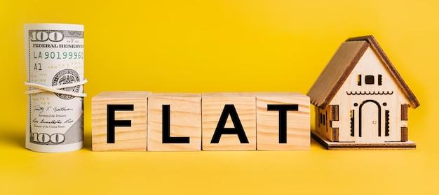 黄色の背景に家のミニチュアモデルとお金のフラット。ビジネス、金融、クレジット、税、不動産、住宅、住宅の概念