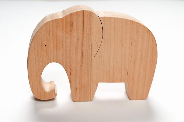 Плоский деревянный слон на белом фоне.
