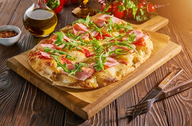Flatbread pizza with ham and arugula on a dark wooden table