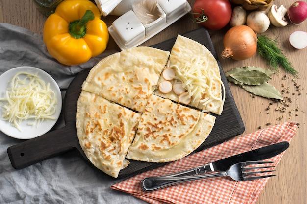 木製のまな板にソーセージとモッツァレラチーズを詰めたフラットブレッド