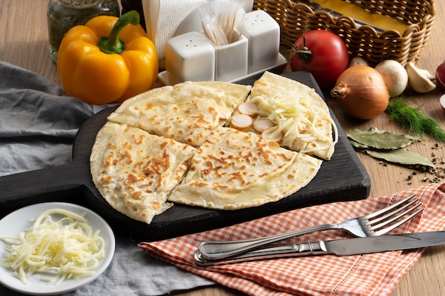 Flatbread with sausage and mozzarella cheese filling on a wooden cutting board