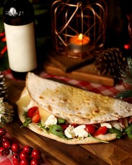 Flatbread wrap filled with cherry tomato arugula and mozzarella