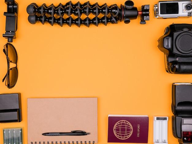 パステルオレンジの背景に旅行ブロガーのフラットレイアクセサリー。 dsrlとアクションカメラ、フラッシュ、三脚、バッテリー付き充電器、紙のノートとパスポート。上面図