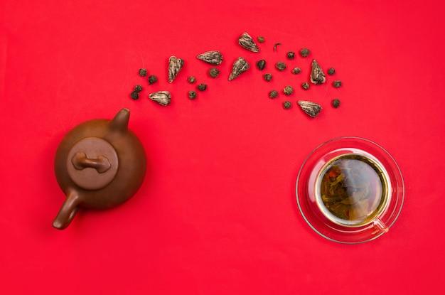 中国の粘土のティーポットとガラスのコップに落ちる緑茶のフラットレイアレンジ。赤の背景。