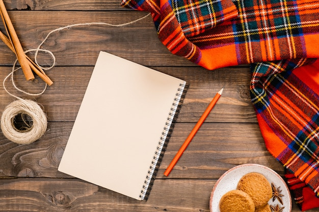 Flatlay autumn composition. women fashion red scarf, paper notepad with empty page, pen, cookies