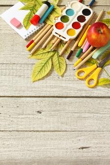 Flatlay фон стол с осенними листьями, яблоком и школьными принадлежностями