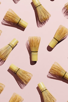 Flatlay of bamboo matcha tea whisks on pink pastel background
