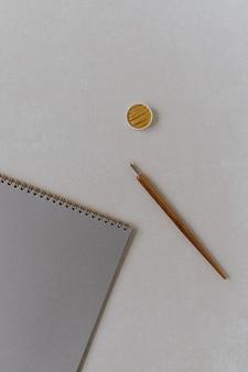 Flatlay blank paper sheet notebook, fountain pen, golden ink on beige concrete surface