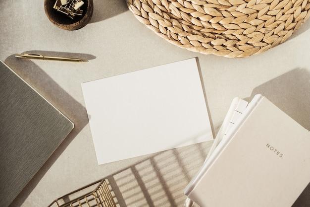 Flatlay 빈 종이 시트, 노트북, 나무 그릇에 클립, 베이지 색 콘크리트 표면에 짚 스탠드