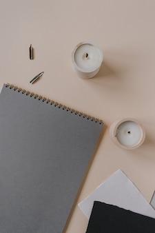 Flatlay blank paper sheet pad, fountain pen, ink on beige background. minimalist home office desk workspace.