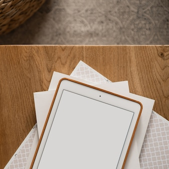 Flatlay of blank screen tablet pad, paper sheets on wooden table and carpet