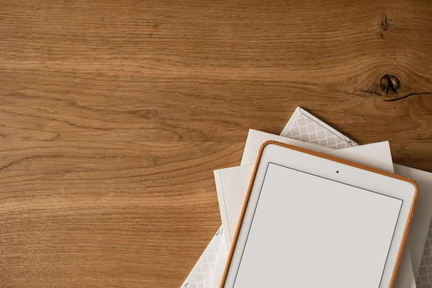 Flatlay of blank screen tablet pad, paper sheets on wooden