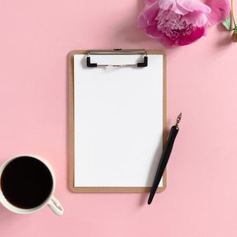 Flatlay of clipboard mockup, mug of coffee, calligraphy pen, peony flower on a pink pastel background
