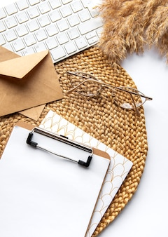 Flatlay of clipboard with blank paper sheet. keyboard, pampas grass, stationery on beige straw background. minimalist home office desk workspace. top view mockup copy space.