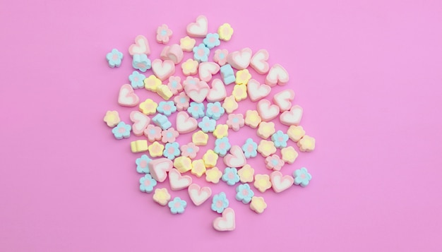 Flatlay colorful marshmallows on sweet pink background with copy space