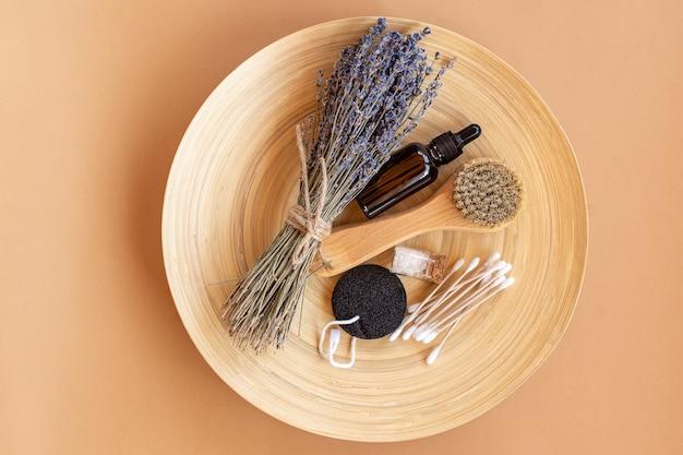 라벤더 꽃과 천연 화장품으로 구성된 플랫레이 구성. 유기농 스파 화장품. 얼굴 세럼, 에센셜 오일, 마사지 얼굴 브러시, 스폰지, 바다 소금, 대나무 귀 스틱이 나무 접시에 있습니다.