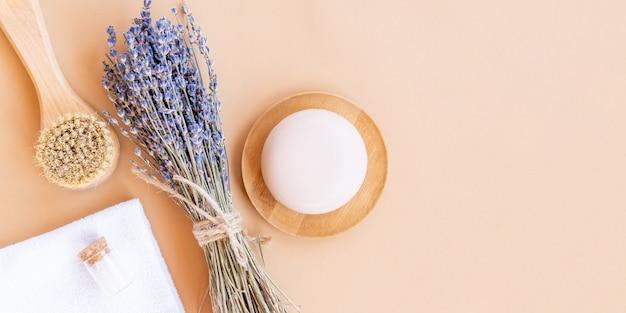ラベンダーの花と天然化粧品を使用したフラットレイ組成物。オーガニックspa化粧品。ベージュの背景にフェイスブラシ、ソープバー、海塩、竹タオルをマッサージします。バナー