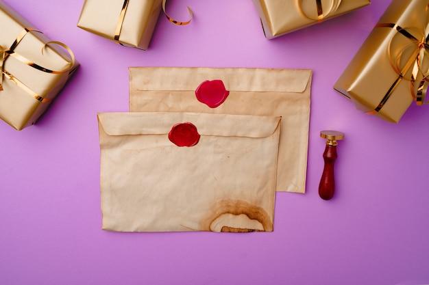 Композиция flatlay со списком санты и упакованными подарочными коробками на фиолетовом фоне, вид сверху