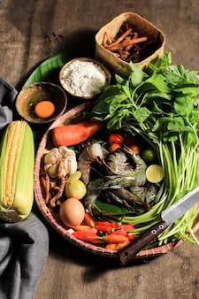 フラットレイ調理材料の準備、ほうれん草のスープ(sayur bayam)とエビの天ぷらを作ります。テキスト/広告用のコピースペースを備えた生の新鮮な食材の構成