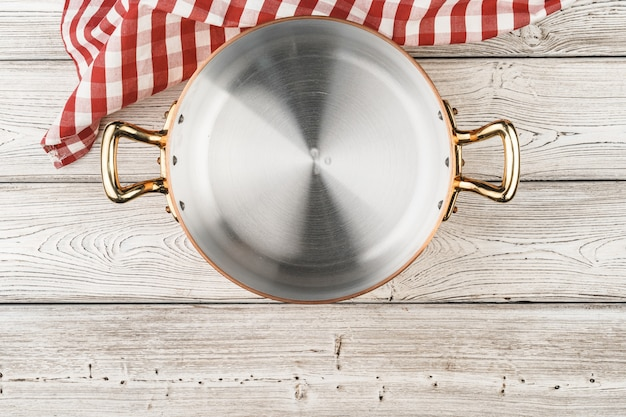 Flatlay of copper cooking pot on wooden table