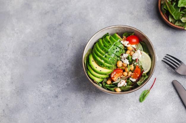 Зеленый салат с рукколой, авокадо, нутом, тмином, мангольдом, помидорами, лаймом, творогом, семенами льна и кунжута, оливковым маслом, обожженным на сером фоне зеленой льняной салфеткой. flatlay с copyspace