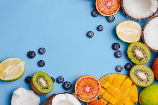 Набор тропических фруктов киви, апельсин, кокос, манго, черника, лайм, киви на синем фоне. пищевая рамка. flatlay с copyspace. концепция иммунитета