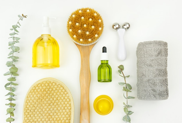 A flatlay of face oil and face roller, brush for massage, cotton towel and brunches of eucalyptus
