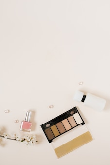 Flatlay fashion blogger spring desk frame with woman cosmetic on beige background. top view