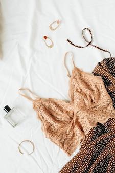 白いリネンの上にフラットレイのファッショナブルな女性の下着、服、アクセサリー。生姜ブラ、ドレス、香水、イヤリング、ブレスレット、枕
