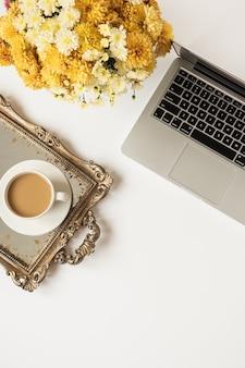 ラップトップコンピューター、コーヒーカップ、白いテーブルの上の美しい花の花束とフラットレイ女性の最小限のワークスペース。上面図
