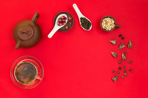 中国の緑茶の葉、バラのつぼみ、ジャスミンの花と粘土のティーポットのflatlayフレームの配置。赤の背景