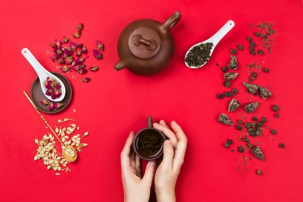中国の緑茶の葉、バラのつぼみ、ジャスミンの花、ティーポット、ティーカップを持っている女性の手が入ったflatlayフレームの配置。赤の背景