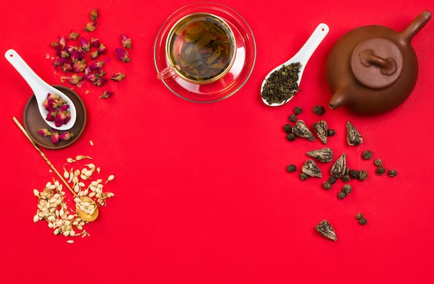 Flatlay frame arrangement with chinese green tea, rose buds, jasmine flowers and dry tea leaves. red background. copyspace