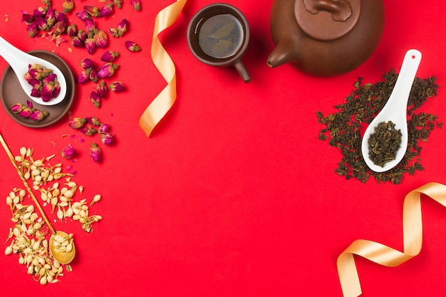 Flatlay frame arrangement with chinese green tea, rose buds, jasmine flowers and golden ribbons. red background. copyspace