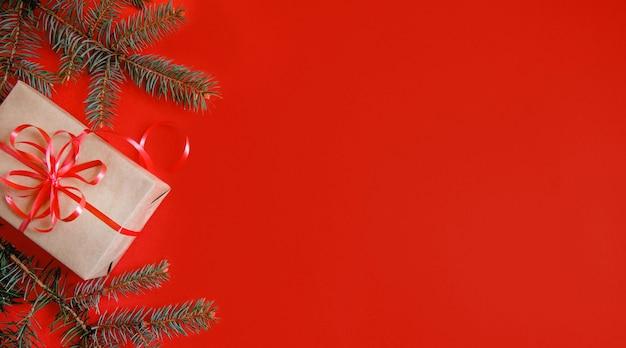 공예 종이, 빨간 리본 및 빨간색 배경에 전나무 지점에서 크리스마스 선물에서 flatlay. copyspace와 배너