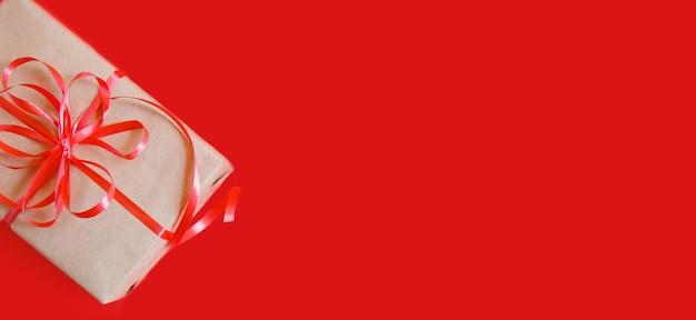 Flatlay от рождественского подарка в крафт-бумаге с красной лентой на красном фоне. баннер с copyspace
