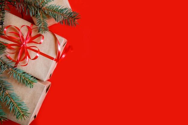 クラフト紙、赤いリボン、赤い背景のモミの枝のクリスマスプレゼントからフラットレイ。コピースペース