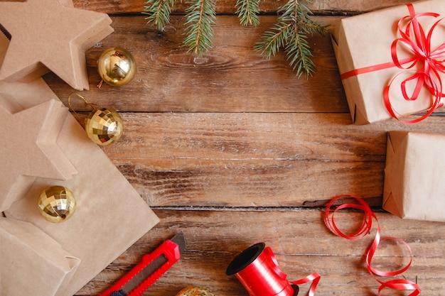 Флэтлей из новогодних подарков в крафт-бумаге, красной ленте, канцелярском ножике, золотых шарах и еловой ветке на деревянном столе