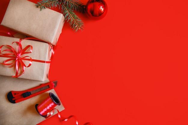 クラフト紙、赤いリボン、文房具のナイフ、赤い安物の宝石と赤い背景の上のモミの枝のクリスマスプレゼントからフラットレイ