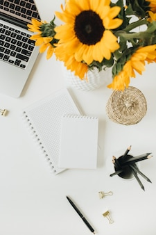 Flatlay of home office desk workspace with laptop, notebook, yellow sunflowers bouquet on white