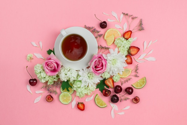 Flatlay of hot cup of tea with various berries and flowers
