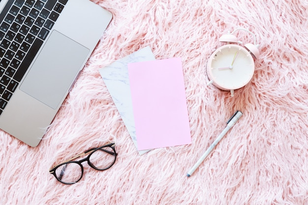 Flatlay of laptop, women knitted sweater, reading glasses, paper